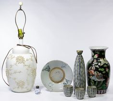 Lot 461: Asian Ceramic Object Assortment; Including a white ceramic lamp with bisque slip decoration, a Chinese black ground vase, a Japanese sake decanter with three cups, a blue and white rimmed bowl and a blue and white shaker