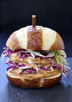 This BBQ Bang Bang Burger is stacked high with crisp slaw and covered with bbq bang bang sauce!