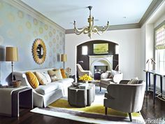 "On the living room wall in an Atlanta house designed by Kristin Kong, Versa's Medici vinyl wallcovering ""brings gold and silver together in an iridescent way,"" Kong says. Metallic colors are carried through the room with pillows in Bernhardt fabrics and Bernhardt's Candide sofa, Surya's Modern Classics rug, Arteriors' Prescott mirror and Neal table lamps, and Gabby's Sutton coffee table and Monroe chairs. HB's Paint Picks: Ceremonial Gold, Griffin, and Kestrel White, all by Sherwin-Williams."