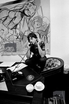 Paul McCartney smoking on the telephone with a painting behind him.