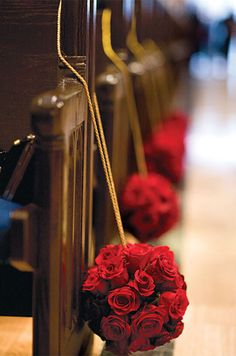 Pomanders of red roses decorate the pews of this wedding ceremony. Floral by Enchanted Florist & Boutique; Photo by Jeffrey and Julia Woods