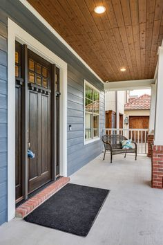 A Cozy Covered Front Porch With Recessed Lighting