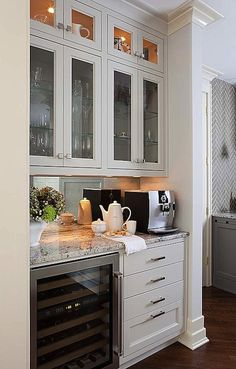 Kitchen Coffee Station Features Lit Display Cabinets And Glass Front Inset Paired With White Gray Granite Countertops