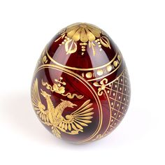 "This red hued Crystal Faberge Egg was hand-blown and engraved in Saint Petersburg, Russia. It has a beautiful semi-transparent appearance and is encrusted with 22-carat gold. It is about 3 3/4"" tall and makes a very special Easter Egg gift. Due to the hand-made nature of this product, designs may slightly vary between each egg."