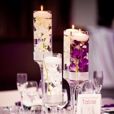 One of the centerpieces at the reception consisted of tall candle holders filled with white and purple orchids with floating candles. The table numbers were a DIY project the bride and groom did themselves.