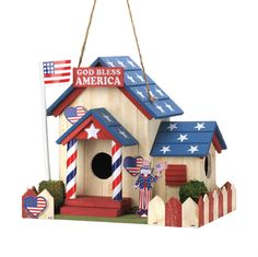 "Uncle Sam is ready to welcome some feathered friends to your yard! This darling birdhouse is filled with patriotic charm, featuring an American flag flying high from the flag pole, stars on the roof, and a red and white picket fence. Two entrances and heart-shaped decorations will make your birds feel right at home in the U.S.A!  8½"" x 6½"" x 8¼"" high.  Wood."