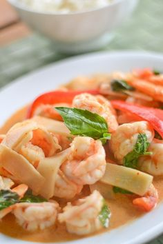 The shrimp in this shrimp curry recipe are cooked in a red creamy sauce. The sliced bamboo shoots, bell pepper strips and basil leaves complete this dish.