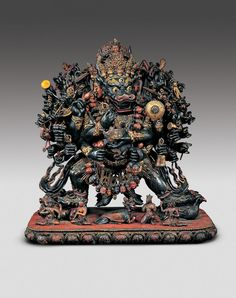 VMFA Sino-Tibetan Yamantaka Vajrabhairava-- A garland of severed heads, symbolizing the conquest of the ego, hangs from his neck. The implements in his thirty-four hands represent different aspects of spiritual knowledge. Many are weapons that he uses to destroy various obstacles to Enlightenment. This otherwise terrifying deity is a cosmic emanation of Manjushri, the bodhisattva of wisdom, whose serene face emerges from Yamantaka's crown.