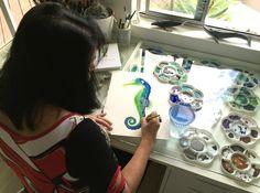 Cindy Lane painting at her studio desk