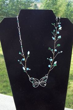 Butterfly Necklace by Laura Lattin - Wire wrapping & wire twisting, and, really, just a few beads (on a background of a single line of little beads that hide the wire). i like the asymmetry and the delicacy