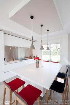 Une cuisine design italien total look blanc avec îlot central, à la fois coin repas conviviale et espace de travail