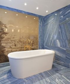 The master bathroom boasts blue marble and a tub from Waterworks. Glass protects an antique hand-blocked panel from Gracie.