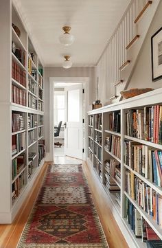 Hallway lined with bookshelves and oriental rug runner