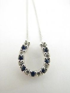 A 14K white gold horseshoe pendant necklace with seven round sapphires and eight round diamonds #wickliffauction