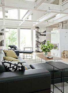 Olohuoneessa on Tapion Interfacelle suunnittelemia Väre- ja Wire-malliston kalusteita, ja valaisimet ovat Keraplastin Tip-sarjaa. Uuniseppien varaavan takan vieressä on halkotelineenä Tapion Showroom Finlandille suunnittelema Mixrack-säilytin. Kaikki tekstiilit ovat Vallilasta. | Koti täynnä kokeiluja | Koti ja keittiö