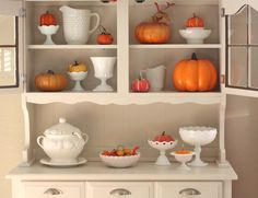 Lovely Fall display, and a great example of how you can pull off something stylish on a serious budget. (Goodwill Hutch with milk glass and pumpkins for Fall.)