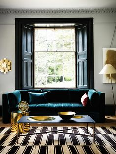 The lustre of brass elements shine brightly when set against a calm backdrop of cool greys. A deep emerald green velvet sofa adds to the sense of drama and richness.