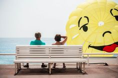 Two vacationers are sitting on a bench of the Promenade des Anglais watching the parasailing taking off from one of the many beaches in Nice.