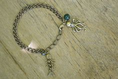 """Bracelet """"Abysses"""" en bronze et sa perle naturelle de jade, composé d'une pieuvre et d'un squelette. #bijoux #bracelet #faitmain #julesverne"""