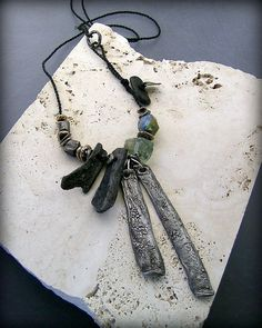 duets fossil collage - steel and bronze, fossilized bone, green amethyst and Basha bead - kathy van kleeck