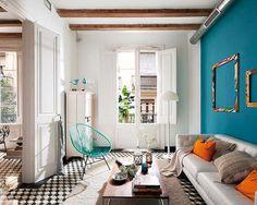 ブルーの壁に映える、オレンジのクッションが印象的なインテリア。