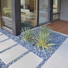 Like a walk by the river, curves of the simple river rounds look great next to the perfectly straight pavers. Cool grey colours make the walkway a very tranquil transition