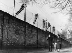 East Berlin border guards adding barbed wire to the newly built Berlin Wall.