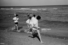 British pop group the Beatles, (L-R) George Harrison (1943 - 2001), Ringo Starr, John Lennon (1940 - 1980), and Paul McCartney, run along a beach while several swimmer watch from the water, Miami Beach, Florida, February 1964.