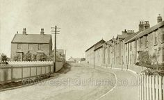South Hetton, East Front Street. This view is of the Easington to Wardley road (later A182), with what was, after nationalisation of the mines, to become the Colliery Manager's house (South Lodge?) prominent on the left and the Colliery Offices opposite.  The manager's house was subsequently sold to a Surveyor of Customs & Excise and later became a residential home for retired people.  The camera is pointing west-north-westward.  Visible beyond the telegraph pole are the Miners' Institute…