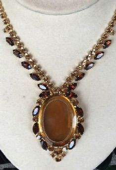 Vintage costume necklace of amber and topaz rhinestones highlighting a cut glass pendant. All prong set, like fine jewelry. 1950s.