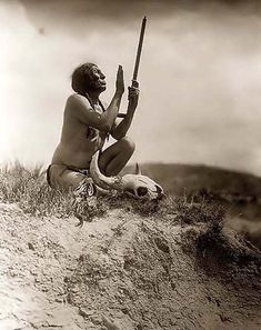 Slow Bull Praying to the Great Spirit. It was created in 1907 by Edward S. Curtis.    The photograph presents Slow Bull,  holding pipe with mouthpiece pointing skyward, buffalo skull at his feet.