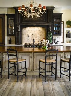 This black cabinetry is accented with gray heavily distressed island and reclaimed looking wood floors to create an old world look, Habersham