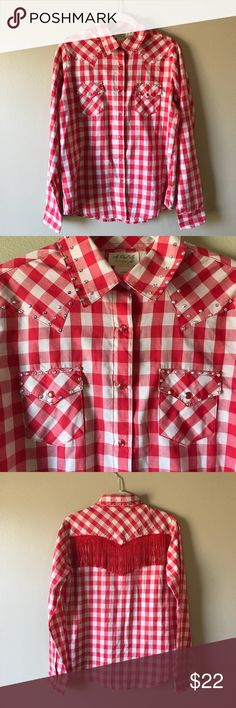 """Wrangler Red Gingham Custom Bedazzled Western Top Custom bedazzled red gingham western cowgirl shirt. Snap down front. Chest snap pockets. Clear crystals added at collar and neckline and fringe added to the back. Shirt is by As Real As Wrangler and is labeled as a size M. Measures 22"""" armpit to armpit and 25"""" shoulder to longest point of front hem. In excellent condition. Wrangler Tops Button Down Shirts"""