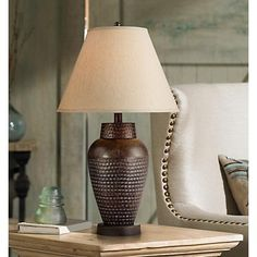 Add light and attractive style to any room with this bronze table lamp. The design is attractive with a beautiful hammered texture.
