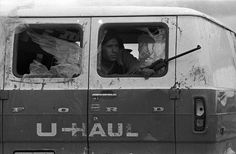 AIM militant with his weapon inside stolen U-Haul van. AIM used the van during shootouts with the FBI during the siege that left the van bullet riddled and windows broken, 1973.  Photo credit: Jim Hubbard