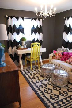 Gray office with white/black curtains, yellow chair, white desk, wood console, blue lamp, metallic poufs, and pink pillows. Eclectic Home Office eclectic home office
