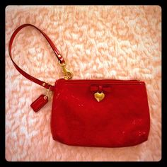 Red Patent Leather Coach Wristlet Like new without tag. Gold tone accents. Heart shaped Coach branded heart dangles from red patent leather bow. Coach Bags Clutches & Wristlets