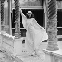 A model wearing a full-length white dress with matching hat, at a show by British designers Bill Gibb, John Bates, Jean Muir and Zandra Rhodes, at Les Ambassadeurs, 1972.