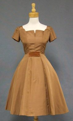 "A nice 1950's cocktail dress in a dark camel colored silk taffeta backed in organdy. Short sleeved dress with sculptural bust. Velvet band tucked inside the bust and another at both front and back waist. Dress has a full skirt (shown here with a crinoline... not included). Interior waistband with hook/eye. Label reads, ""Harold."""