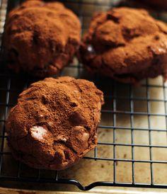 Składniki na około 15 – 20 ciasteczek:      200g gorzkiej czekolady 70% kakao     50g niesolonego masła     2 jajka     150g jasnego cukru muscovado     25g mąki pszennej     10g ciemnego kakao     1/4 łyżeczki proszku do pieczenia     szczypta soli  Dodatkowo:      75g ciemnej czekolady, z grubsza posiekanej     75g posiekanych orzechów włoskich     kakao do oprószenia  Wykonanie:  Czekoladę posiekaj i umieść razem z masłem w żaroodpornej miseczce nad rondelkiem z gotując...