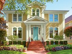 A baby blue door framed by white columns livens up the entry to this butter-yellow Italiante home. | Courtesy of: Valspar Paint | thisoldhouse.com