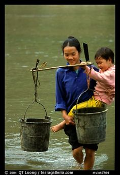 Woman of the Tay minority carrying water crossing the river with child, Ba Be Lake. Vietnam