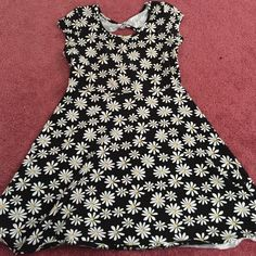 Black Spring Dress with White Floral Daisy Pattern Really cute spring dress! Black with white and yellow daisies. Has a twist and small opening in the back. More of a stretchy material for a really comfortable fit! Cute with a nice pair of sandals or wedges and a jean jacket! No signs of wear, stains, or damages of any sort. Smoke free home. Dresses