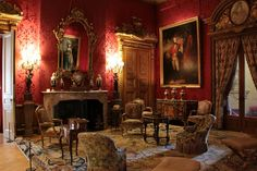Waddesdon Manor: The Red Drawing Room. This room is at the center of the garden front. This is where callers would be received, and guests assembled here before dining next-door. George IV as Prince of Wales presides, as painted by Gainsborough. Lady Sheffield by the same artist peeks out of the mirror. JC