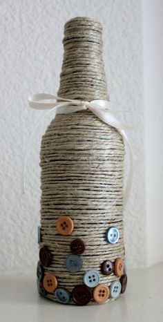 DIY  bottle decor - a beer bottle, hemp cord, hot glue, buttons, and ribbon!