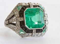 Colombian Six Carat Emerald Platinum Ring. This magnificent ring features a 6.11 carat Columbian Emerald that has been certified by AGL. The ring contains emerald accents, onyx and diamonds. Art Deco or Art Deco style