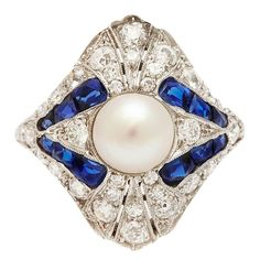 Art Deco Natural Pearl Diamond Sapphire Ring. Ornate Art Deco bombé ring set with a central natural pearl, pavé diamonds and calibré sapphires, mounted in platinum.