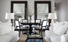 living room dining room design with espresso stained wood floor mirrors, black round pedestal dining table, white  black nailhead trim dining chairs