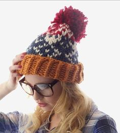 Add some fun flair to your winter wardrobe with this chunky pompom hat.