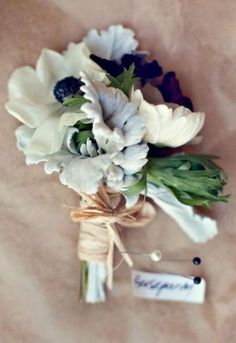 The corsages will be a combination of white anemones and grey dusty miller wrapped in raffia with the stems showing.